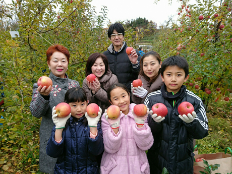 顔の横にりんごを持っている家族